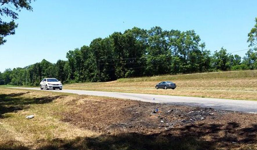 FILE - In this June 7, 2016, file photo cars pass charred ground remnants at the scene of a fatal traffic accident in rural Tuscaloosa County, Ala. Lawyers James Halsell, the retired NASA astronaut charged with murder in a fatal car crash that killed two young sisters, contend tests reveal there wasn't any alcohol in his system, court documents show. Attorneys for Halsell filed a motion including the test results Thursday, Jan. 9, 2020. (AP Photo/Phillip Lucas, File)