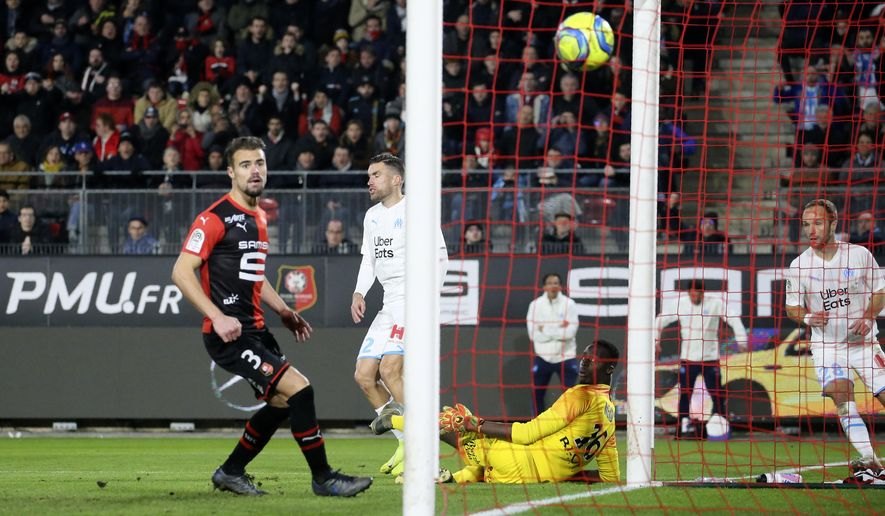 Marseille's Kevin Strootman, second left, scores his side's opening goal during the League One soccer match between Rennes and Marseille, at the Roazhon Park stadium in Rennes, France, Friday, Jan. 10, 2020. (AP Photo/David Vincent)