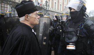 A lawyer faces a riot police officer during a demonstration in Rennes, western France, Thursday Jan. 9, 2020. French rail workers, teachers, doctors, lawyers and others joined the fourth nationwide day of protests and strikes on Thursday to denounce President Emmanuel Macron's plans to overhaul the pension system. (AP Photo/David Vincent)
