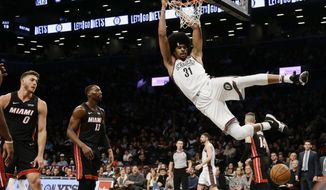 Brooklyn Nets' Jarrett Allen (31) dunks in front of Miami Heat's Bam Adebayo (13), Meyers Leonard (0) and Tyler Herro (14) during the second half of an NBA basketball game Friday, Jan. 10, 2020, in New York. The Nets won 117-113. (AP Photo/Frank Franklin II)