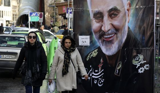 Women walk past a banner of Iranian Revolutionary Guard Gen. Qassem Soleimani, who was killed in Iraq in a U.S. drone attack on Friday, in Tajrish square in northern Tehran, Iran, Thursday, Jan. 9, 2020. Many Iranians say they are relieved that neither their country nor the United States appear primed right now for a more direct military confrontation that could lead to war. (AP Photo/Vahid Salemi)