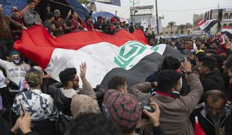Anti-government protesters carry a big Iraqi flag and chant anti-Iran and anti-U.S. slogans during the ongoing protests in Tahrir square, Baghdad, Iraq, Friday, Jan. 10, 2020. (AP Photo/Nasser Nasser)
