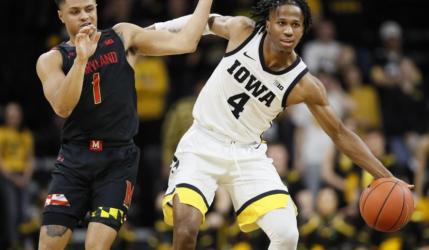 Iowa guard Bakari Evelyn drives upcourt past Maryland guard Anthony Cowan Jr., left, during the second half of an NCAA college basketball game, Friday, Jan. 10, 2020, in Iowa City, Iowa. (AP Photo/Charlie Neibergall)