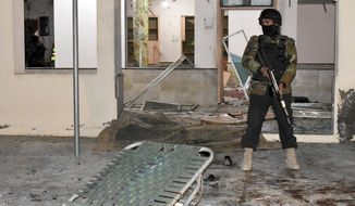 Pakistani police officer stands guard at the site of bomb explosion in a mosque in Quetta, Pakistan, Friday, Jan. 10, 2020. A powerful explosion ripped through a mosque in southwest Pakistan during Friday evening prayers, killing a senior police officer with some civilians and wounded other worshipers, police said. (AP Photo/Arshad Butt)