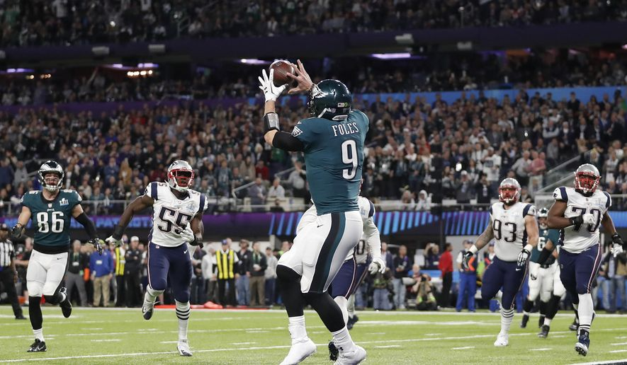 In this Feb. 4, 2018, file photo, Philadelphia Eagles' Nick Foles catches a touchdown pass during the first half of the NFL Super Bowl 52 football game against the New England Patriots, in Minneapolis. Coaches aren't shy about drawing up trick plays that let quarterbacks use their hands for more than throwing a football. (AP Photo/Jeff Roberson, File)  **FILE**