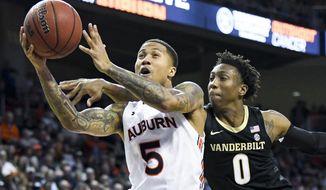 Vanderbilt guard Saben Lee (0) defends a drive to the basket by Auburn guard J'Von McCormick (5) during the second half of an NCAA college basketball game Wednesday, Jan. 8, 2020, in Auburn, Ala. (AP Photo/Julie Bennett)