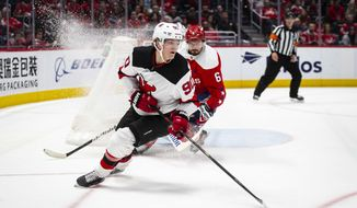 New Jersey Devils center Jesper Boqvist (90), from Sweden, moves the puck past Washington Capitals defenseman Michal Kempny (6), from the Czech Republic, during the third period of an NHL hockey game Saturday, Jan. 11, 2020, in Washington. The Devils won 5-1. (AP Photo/Al Drago)