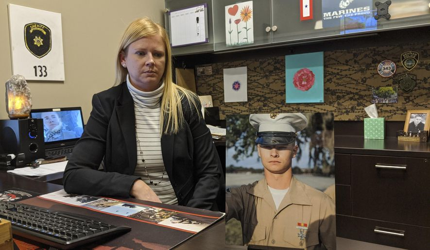 In this Jan. 5, 2020 photo, Coweta County Investigator Shawna Wade displays a photo of her son, Lance Corporal Collin Wade, currently serving in the Middle East.   ( Clay Neely/The Newnan Times-Herald via AP)
