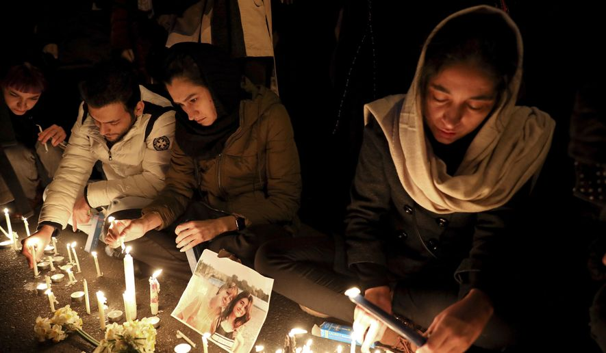 "People gather for a candlelight vigil to remember the victims of the Ukraine plane crash, at the gate of Amri Kabir University that some of the victims of the crash were former students of, in Tehran, Iran, Saturday, Jan. 11, 2020. Iran on Saturday, Jan. 11, acknowledged that its armed forces ""unintentionally"" shot down the Ukrainian jetliner that crashed earlier this week, killing all 176 aboard, after the government had repeatedly denied Western accusations that it was responsible. (AP Photo/Ebrahim Noroozi)"