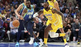 Dallas Mavericks guard Tim Hardaway Jr. (11) gets the ball away from Los Angeles Lakers forward LeBron James (23) during the first half of an NBA basketball game Friday, Jan. 10, 2020, in Dallas. (AP Photo/Richard W. Rodriguez)