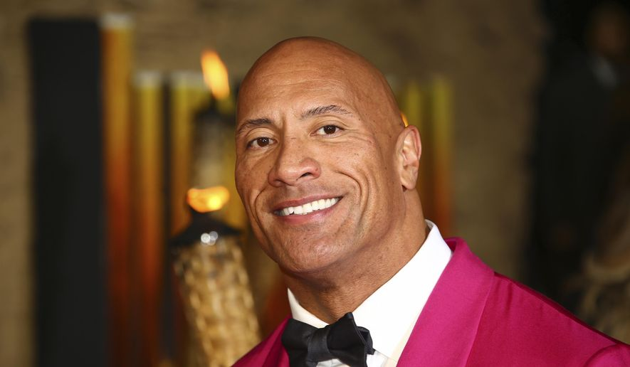 Actor Dwayne Johnson poses for photographers upon arrival at the premiere of the film 'Jumanji The Next Level', in central London, Dec. 5, 2019. (Photo by Joel C Ryan/Invision/AP) ** FILE **