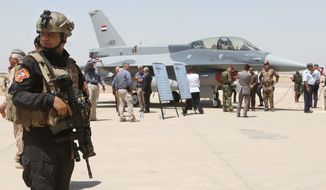 A member of the Iraqi SWAT team stands as security forces and others gather next to one of four new U.S.- made F-16 fighter jets during the delivery ceremony at Balad air base, 75 kilometers (45 miles) north of Baghdad, Iraq, Monday, July 20, 2015. (AP Photo/Khalid Mohammed)