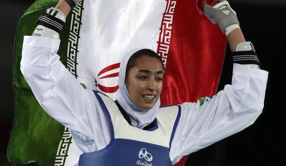 Kimia Alizadeh Zenoorin of Iran celebrates after winning the bronze medal in a women's Taekwondo 57-kgcompetition at the 2016 Summer Olympics in Rio de Janeiro, Brazil, Thursday, Aug. 18, 2016. (AP Photo/Andrew Medichini)