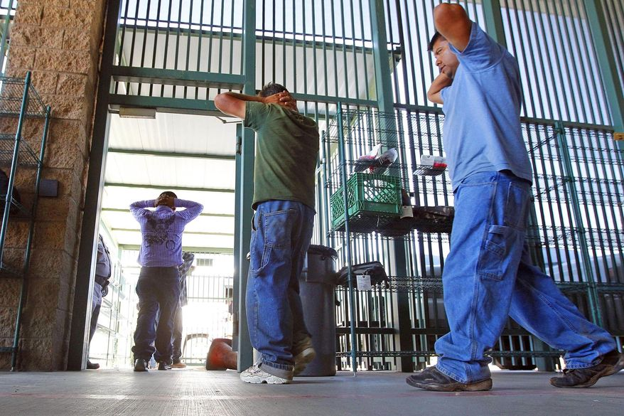 In this Aug. 9, 2012, file photo, suspected illegal immigrants are transferred out of the holding area after being processed at the Tucson Sector of the U.S. Customs and Border Protection headquarters in Tucson, Ariz. (AP Photo/Ross D. Franklin, File)