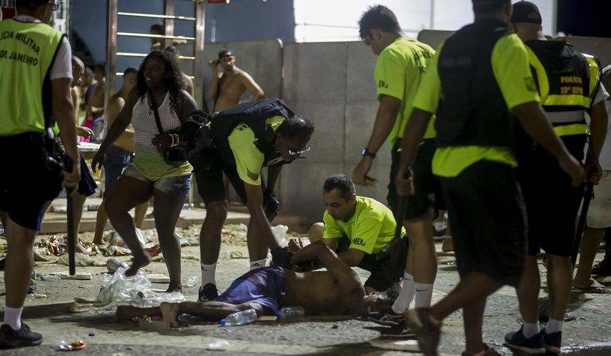 Police officers detain a man during clashes between police and party-goers after the official start of Carnival, on Copacabana beach, Rio de Janeiro, Brazil, Sunday, Jan. 12, 2020. Police officers and municipal guards dispersed attendees with gas bombs, and moments of tension were experienced in the deconcentration of the event, which brought together hundreds of thousands of people. (AP Photo/Bruna Prado)