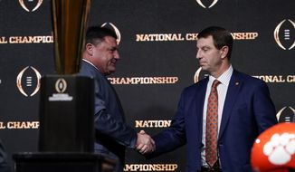 LSU head coach Ed Orgeron, left, and Clemson head coach Dabo Swinney shake hands after a news conference for the NCAA College Football Playoff national championship game Sunday, Jan. 12, 2020, in New Orleans. Clemson is scheduled to play LSU on Monday. (AP Photo/David J. Phillip).