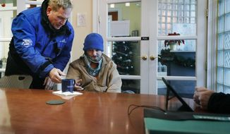 In this Dec. 18, 2019 photo, Rich Northup a Capital Crossroads safety ambassador gets a cup of coffee for Rob Duffy as he checks him in at Capital Crossroads office in Columbus, Ohio. (Eric Albrecht/The Columbus Dispatch via AP)