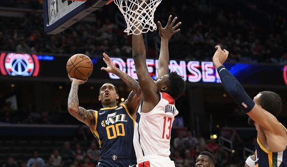 Utah Jazz guard Jordan Clarkson (00) goes to the basket next to Washington Wizards center Thomas Bryant (13) during the first half of an NBA basketball game, Sunday, Jan. 12, 2020, in Washington. (AP Photo/Nick Wass)