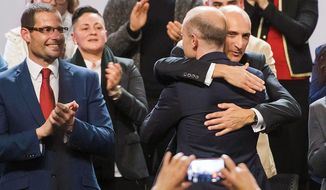 FILE - In this Friday, Jan. 10, 2020 file photo, Maltese Prime Minister and Labour Party leader Joseph Muscat, back to camera at right, is hugged by party member Chris Fearne during a party general assembly where he delivered his farewell speech as party leader in Kordin, near Valletta. At left party member Robert Abela. A new leader will be elected during the weekend. (AP Photo/Rene Rossignaud, File)