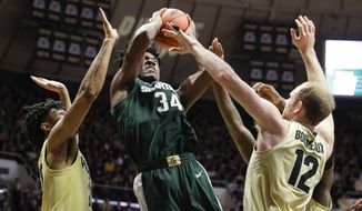 Michigan State forward Julius Marble (34) is defended by Purdue forward Evan Boudreaux (12) and Purdue guard Nojel Eastern (20) as he shoots during the first half of an NCAA college basketball game in West Lafayette, Ind., Sunday, Jan. 12, 2020. (AP Photo/Michael Conroy)