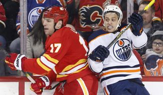 Edmonton Oilers' Caleb Jones, right, reacts to a hit from Calgary Flames' Milan Lucic during the second period of an NHL hockey game Saturday, Jan. 11, 2020, in Calgary, Alberta. (Larry MacDougal/The Canadian Press via AP)