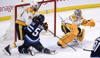 Winnipeg Jets' Mark Scheifele (55) runs into Nashville Predators' Mattias Ekholm (14) in front of Predators goaltender Juuse Saros (74) during first-period NHL hockey game action in Winnipeg, Manitoba, Sunday Jan. 12, 2020. (Fred Greenslade/The Canadian Press via AP)