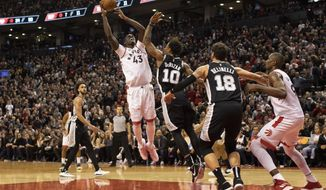 Toronto Raptors forward Pascal Siakam, center, shoots over San Antonio Spurs' DeMar DeRozan during second half NBA basketball action in Toronto on Sunday Jan. 12, 2020. (Chris Young/The Canadian Press via AP)