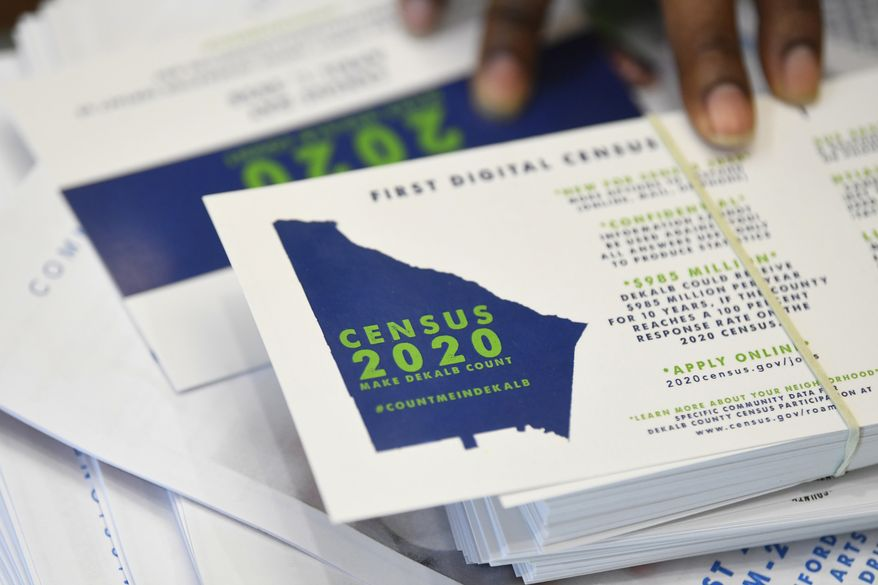 In this Aug. 13, 2019, file photo a worker gets ready to pass out instructions on how to fill out the 2020 census during a town hall meeting in Lithonia, Ga.  (AP Photo/John Amis, File) **FILE**