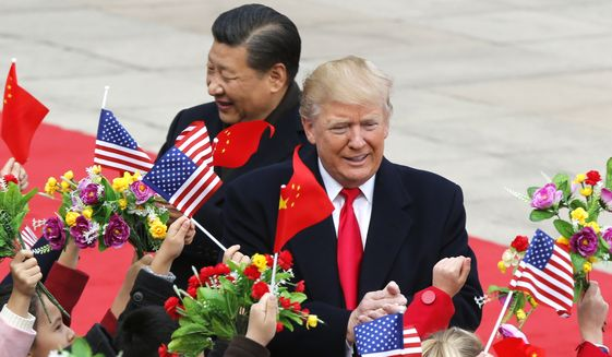 U.S. President Donald Trump, right, and Chinese President Xi Jinping are greeted by children waving flowers and flags during a welcome ceremony at the Great Hall of the People in Beijing, Thursday, Nov. 9, 2017. (AP Photo/Andy Wong)