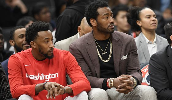 Washington Wizards guard John Wall, right, watches from the bench next to guard Jordan McRae, left, during the first half of an NBA basketball game, Sunday, Jan. 12, 2020, in Washington. (AP Photo/Nick Wass) ** FILE **