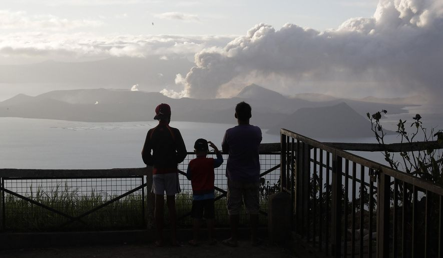 People watch from Tagaytay, Cavite province, south of Manila, as Taal Volcano continues to spew ash on Tuesday, Jan. 14, 2020. Thousands of people fled the area through heavy ash as experts warned that the eruption could get worse and plans were being made to evacuate more. (AP Photo/Aaron Favila)