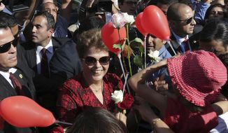 FILE - In this Sept. 6, 2016 file photo, Brazil's impeached President Dilma Rousseff receives flowers and gifts from supporters as she leaves the presidential residence, Alvorada Palace, in Brasilia, Brazil. The Academy Award nomination for a Brazilian documentary about the impeachment of then-President Dilma Rousseff has once again laid bare the polarization of Latin America's largest democracy. (AP Photo/Eraldo Peres, File)