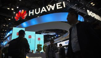 FILE - In this Thursday, Oct. 31, 2019 file photo, attendees walk past a display for 5G services from Chinese technology firm Huawei at the PT Expo in Beijing. Norway's biggest wireless carrier, Telenor, on Friday Dec. 13, 2019, chose Sweden's Ericsson to supply part of its new 5G network, ending its cooperation with Chinese tech giant Huawei after a decade. (AP Photo/Mark Schiefelbein, File)