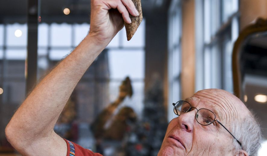 In this Monday, Dec. 16, 2019 photo, Augustana biology professor Craig Spencer holds part of the Bejuco de agua plant at Jones421 in Sioux Falls, S.D. Through the Guatemala Maya Cross Project the plant is harvested in order to create handmade items. The proceeds from the sales are given to the artisans in Guatemala in an effort to reduce the rate of poverty. (Abigail Dollins
