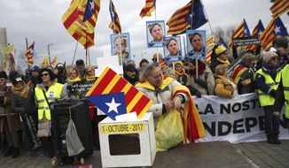 Demonstrators hold signs showing Catalan politician Oriol Junqueras as they protest outside the European Parliament in Strasbourg, eastern France, Monday, Jan. 13, 2020. Catalan leader Carles Puigdemont is expected to attend his first session as a member of the European Parliament on Monday despite facing an arrest warrant against him in Spain. (AP Photo/Francisco Seco)