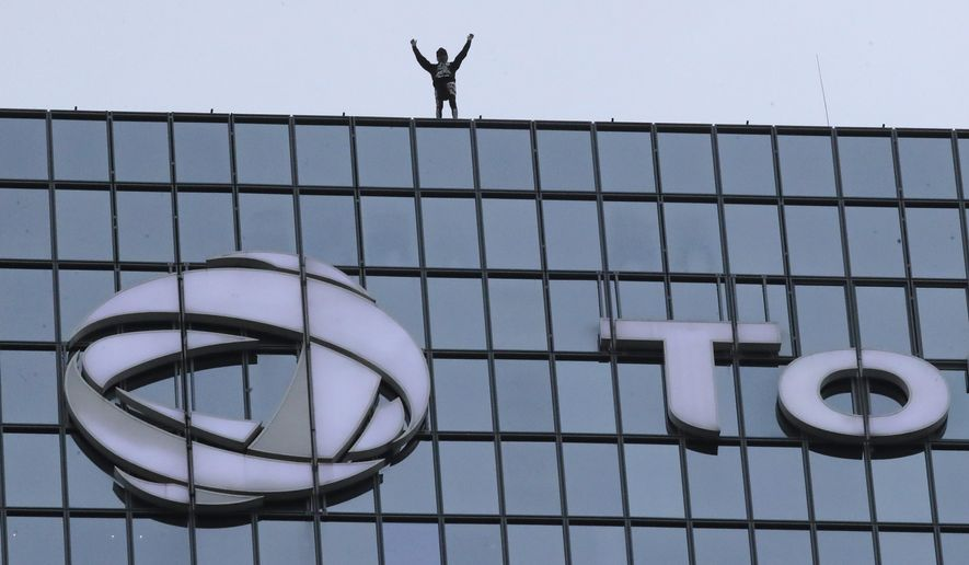 """French urban climber Alain Robert, well known as """"Spiderman"""", raises his arms as he finished to climb the Total tower in the Paris business district of La Defense, Monday, Jan 13, 2020, in support of the transport strikes. (AP Photo/Michel Euler)"""