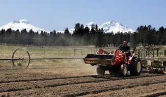 FILE - In this April 23, 2018, file photo, Trevor Eubanks, plant manager for Big Top Farms, readies a field for another hemp crop near Sisters, Ore. Draft rules released by the U.S. Department of Agriculture for a new and booming agricultural hemp industry have alarmed farmers, processors and retailers across the country, who say the provisions will be crippling if they are not significantly overhauled before they become final. (AP Photo/Don Ryan, File)
