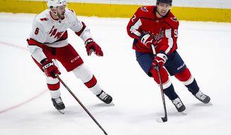 Washington Capitals center Evgeny Kuznetsov (92), from Russia, passes the puck as Carolina Hurricanes defenseman Joel Edmundson (6), Canada, defends during the first period of an NHL hockey game Monday, Jan. 13, 2020, in Washington. (AP Photo/Al Drago)