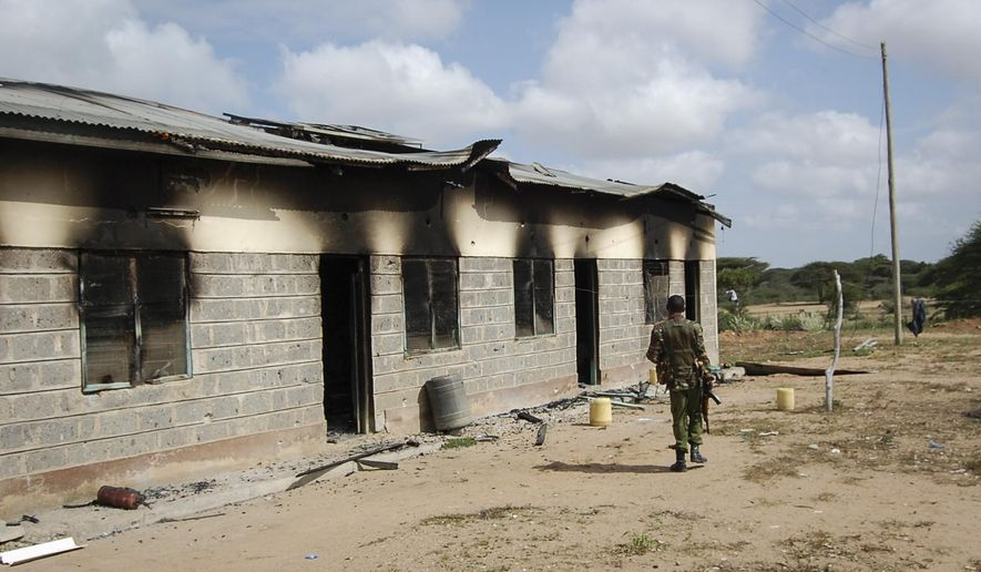 A member of Kenya's security forces walks past a damaged police post after an attack by al-Shabab extremists in the settlement of Kamuthe in Garissa county, Kenya Monday, Jan. 13, 2020. The militants from neighboring Somalia attacked the settlement killing three teachers, setting fire to a police post, and destroying a telecommunications mast, police said in a report seen by The Associated Press. (AP Photo)