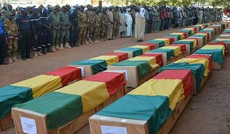 FILE - In this Nov. 20, 2019 file photo made available from the Mali Army, coffins being honoured during a funeral ceremony are pictured in Gao, Mali. As a security summit begins Monday in France with the leaders of Mali, Burkina Faso, Chad, Niger and Mauritania, Macron hopes to counter anti-French sentiment that has bubbled up amid frustration over the extremist attacks that killed thousands of people last year alone. (Mali Army via AP, File)