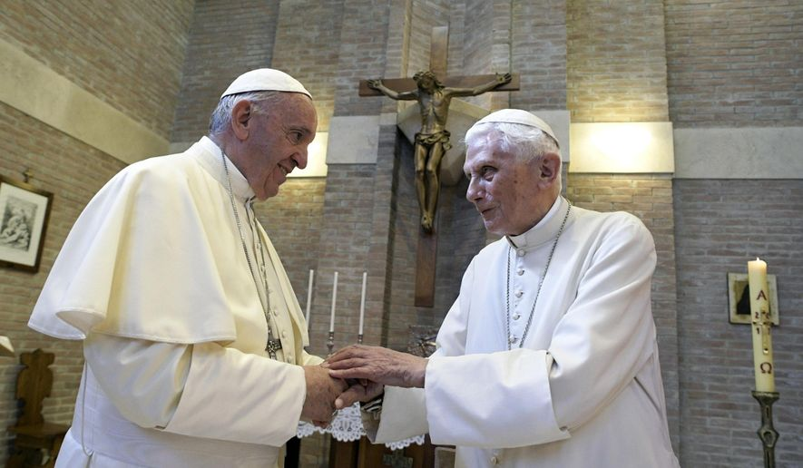 In this June 28, 2017, file photo, Pope Francis, left, and Pope Benedict XVI, meet each other on the occasion of the elevation of five new cardinals at the Vatican. Retired Pope Benedict XVI has broken his silence to reaffirm the value of priestly celibacy, co-authoring a bombshell book at the precise moment that Pope Francis is weighing whether to allow married men to be ordained to address the Catholic priest shortage. (L'Osservatore Romano/Pool photo via AP, File) **FILE**