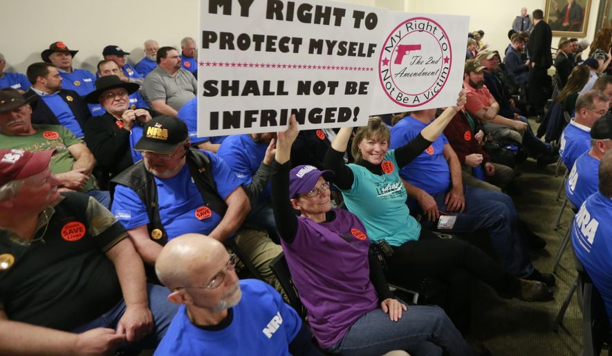 Gun rights protesters hold signs prior to the start of a meeting of the Senate Judiciary committee at the Capitol in Richmond, Va., Monday, Jan. 13, 2020. The Committee passed several bills related to gun laws. (AP Photo/Steve Helber)