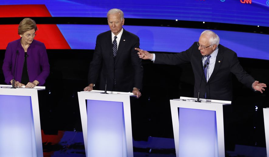 Democratic presidential candidate Sen. Bernie Sanders, I-Vt., right, speaks to Sen. Elizabeth Warren, D-Mass., left, as former Vice President Joe Biden listens Tuesday, Jan. 14, 2020, during a Democratic presidential primary debate hosted by CNN and the Des Moines Register in Des Moines, Iowa. (AP Photo/Patrick Semansky)