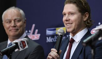 Washington Capitals center Nicklas Backstrom, right, of Sweden, speaks during an NHL hockey news conference about the Capitals re-signing him to a five-year contract, Tuesday, Jan. 14, 2020, in Washington. At left is Capitals general manager Brian MacLellan. (AP Photo/Nick Wass)