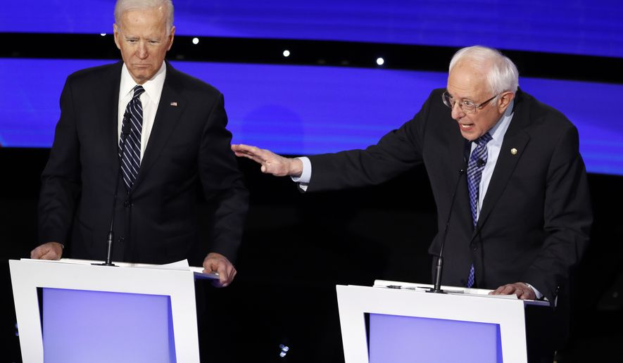 Democratic presidential candidate Sen. Bernie Sanders, I-Vt., right speaks as former Vice President Joe Biden listens Tuesday, Jan. 14, 2020, during a Democratic presidential primary debate hosted by CNN and the Des Moines Register in Des Moines, Iowa. (AP Photo/Patrick Semansky)