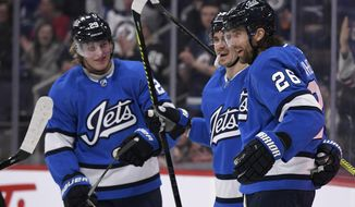 Winnipeg Jets' Blake Wheeler (26) celebrates his goal with teammates Patrik Laine (29) and Mark Scheifele (55) during the second period of an NHL hockey game against the Vancouver Canucks on Tuesday, Jan. 14, 2020, in Winnipeg, Manitoba. (Fred Greenslade/The Canadian Press via AP)