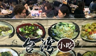 """People are seen in the window eating at a Chinese restaurant decorated with menu items on its shop front on Friday Jan. 10, 2020, in New York City.  A social media campaign backed by a Japanese seasonings company is targeting the persistent idea that Chinese food is packed with MSG and can make you sick. So entrenched is the notion in American culture, it shows up in the dictionary: Merriam-Webster.com lists """"Chinese restaurant syndrome."""" as a real illness. But much of  the mythology around the idea has been debunked: monosodium glutamate, also known as MSG, shows up in many foods from tomatoes to breast milk, and there's no evidence to link it to illness.  (AP Photo/Wong Maye-E)"""