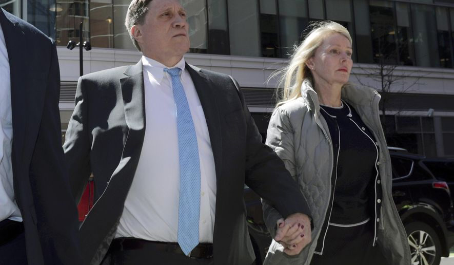 FILE - In this April 3, 2019, file photo, investor John Wilson arrives at federal court in Boston, with his wife Leslie, to face charges in a nationwide college admissions bribery scandal. A federal grand jury in Boston returned an additional indictment charging Wilson with filing a false tax return. (AP Photo/Charles Krupa, File)