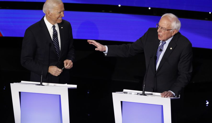 Democratic presidential candidate Sen. Bernie Sanders, I-Vt., speaks as former Vice President Joe Biden looks on Tuesday, Jan. 14, 2020, during a Democratic presidential primary debate hosted by CNN and the Des Moines Register in Des Moines, Iowa. (AP Photo/Patrick Semansky)