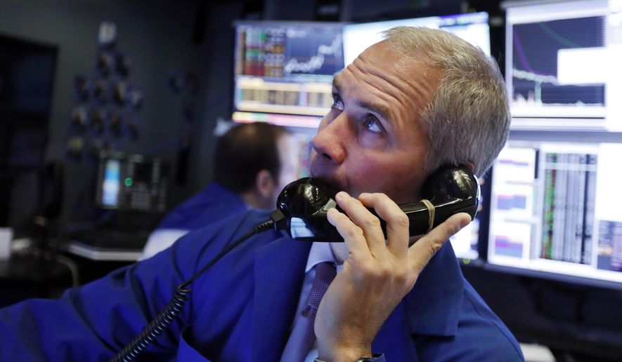 FILE - In this Jan. 9, 2020, file photo trader Timothy Nick works in his booth on the floor of the New York Stock Exchange. The U.S. stock market opens at 9:30 a.m. EST on Tuesday, Jan. 14.  (AP Photo/Richard Drew, File)